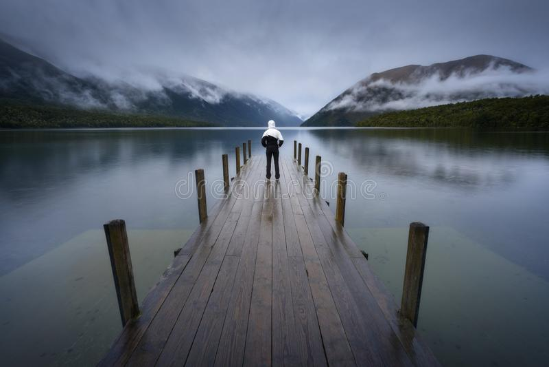 Kobiety sylwetka w Romantycznym nabrzeżu na Jeziornym Rotoiti, widok przegapia mglistą Świątobliwą Arnaud grań, wszystkie część N fotografia stock