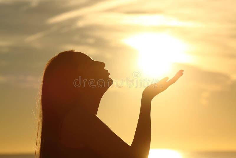 Kobiety sylwetki całowania słońce przy zmierzchem zdjęcia royalty free