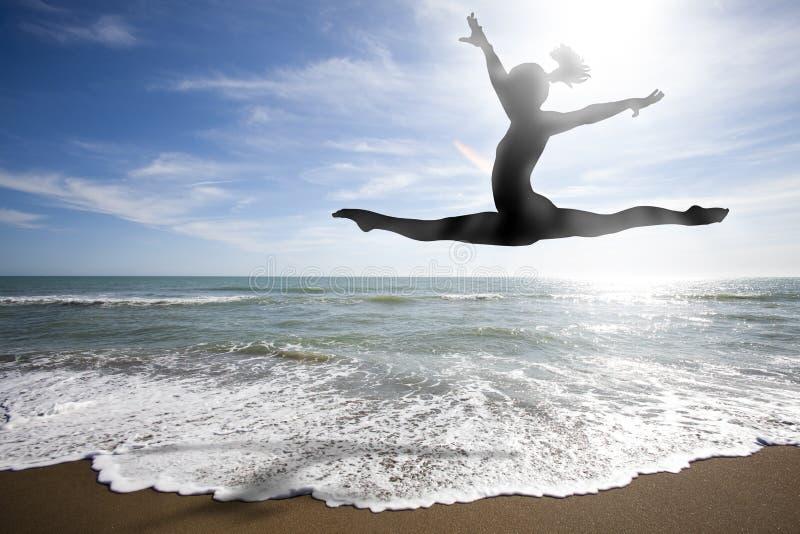 Kobiety sylwetki doskakiwanie za morzem Słońce i plaża obraz stock
