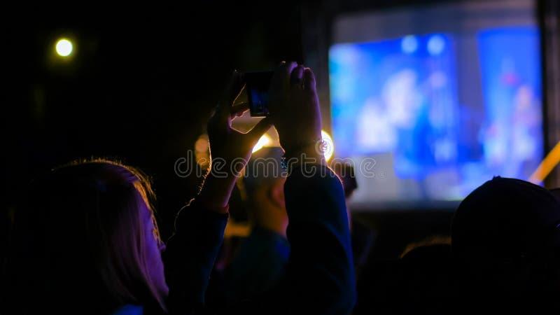 Kobiety sylwetki magnetofonowy wideo muzyka na ?ywo koncert z smartphone obraz royalty free