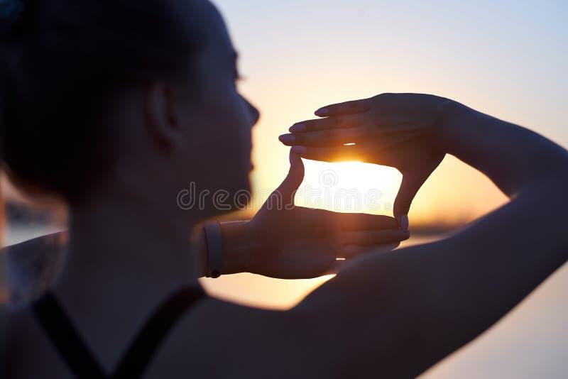 Kobiety sylwetki otokowy słońce z palcami przy zmierzchem Wr?cza kszta?t kamera przez niebo fotografia royalty free