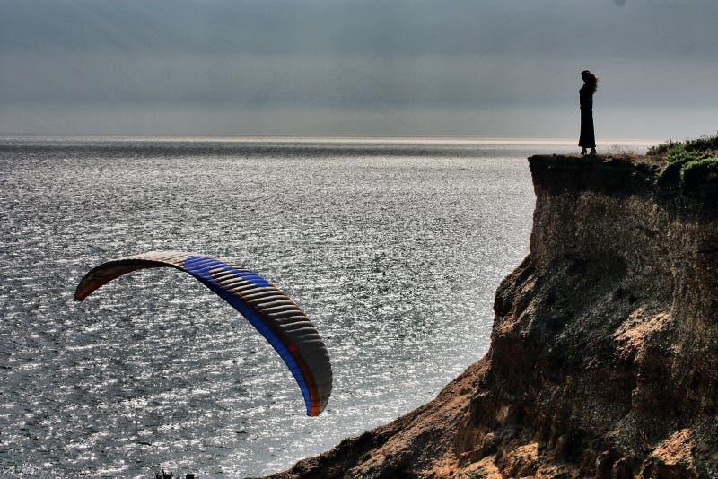 Kobiety sylwetki stać plenerowy na krawędzi falezy dennym brzeg Paraglider na dennym tle zdjęcia royalty free