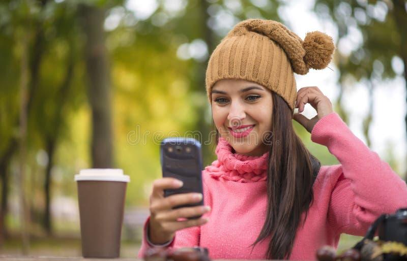 Kobiety szczęśliwa dziewczyna bierze jaźń obrazka selfie z smartphone kamerą outdoors w jesień parku obraz stock