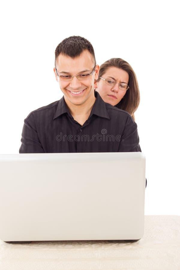 Kobiety szpieguje na mężczyzna podczas gdy gawędzący nad internetem fotografia royalty free