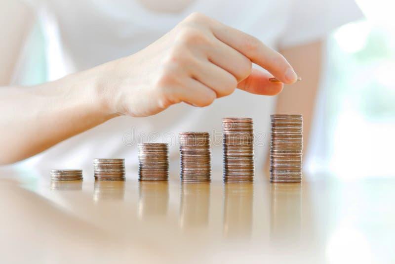 Kobiety sztaplowania monety w wzrastające kolumny fotografia stock
