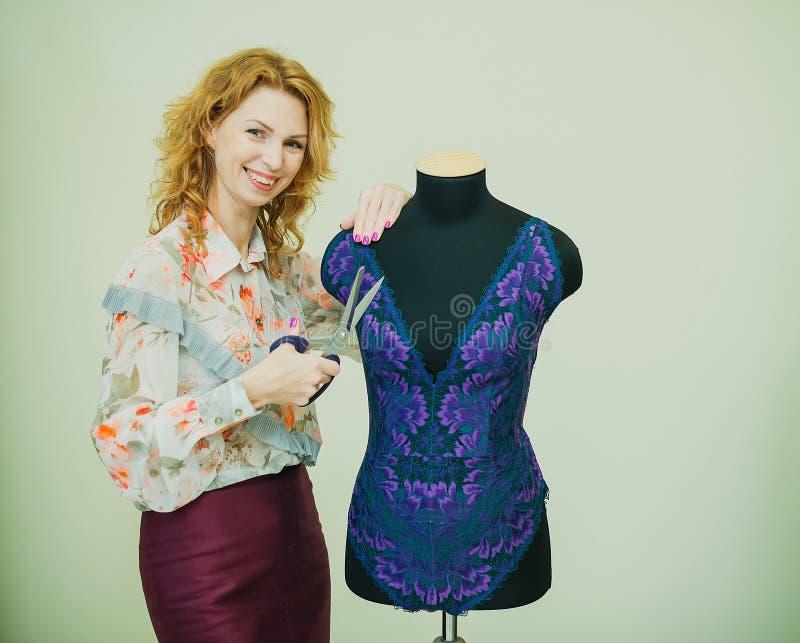 Kobiety szwaczka pracuje w jego studiu Mannequin jest ubranym koronkowego bodysuit obraz royalty free