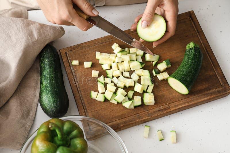 Kobiety Tn?cy Zucchini w kuchni obraz royalty free