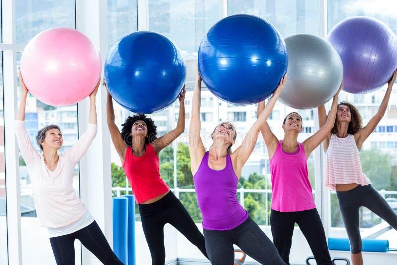 Kobiety trzyma ćwiczenie piłki podnosić z rękami zdjęcia royalty free