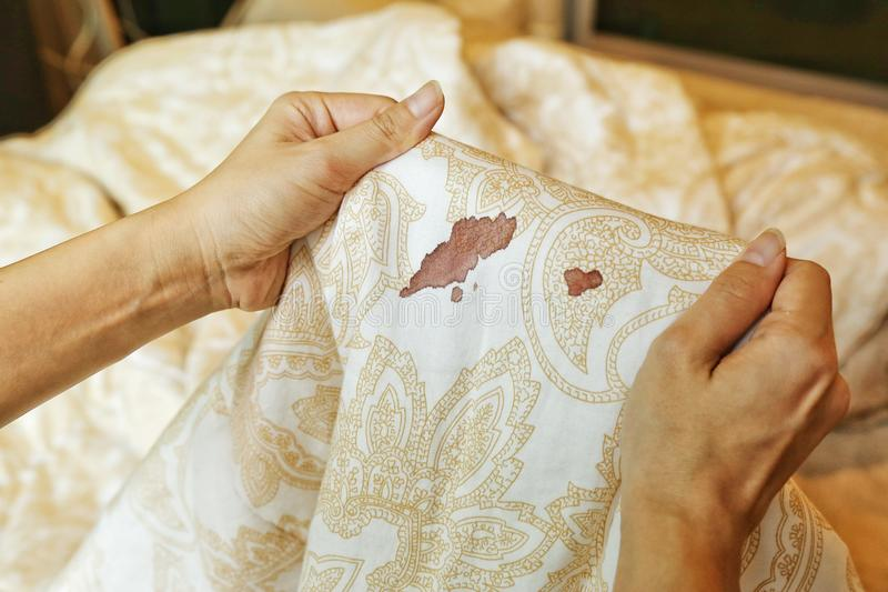 Kobiety trzymają łóżkowego prześcieradło z okresu krwionośnego punktu plamami na plamy tle Potrzeba czyścić obrazy royalty free