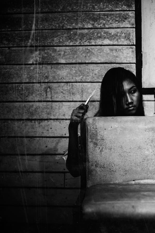 Kobiety trzymają nóż z powrotem krzesło zdjęcie stock