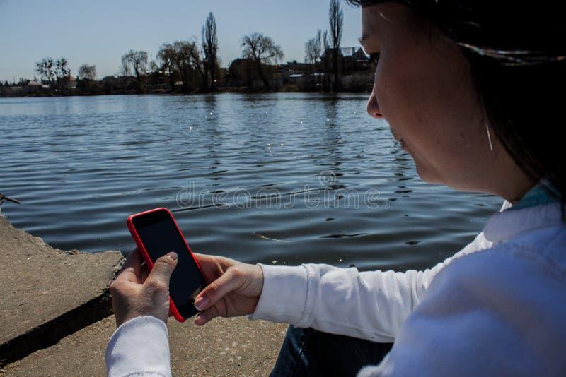 Kobiety trzymają telefon przeciw tłu rzeka zdjęcia stock