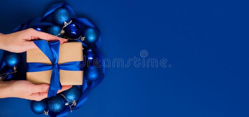 Kobiety trzymające pudełko z wstążką na niebieskim tle zdjęcia royalty free