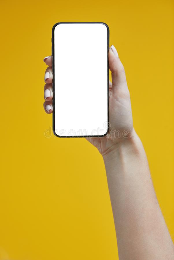 Kobiety trzymające smartfon na żółtym tle fotografia royalty free