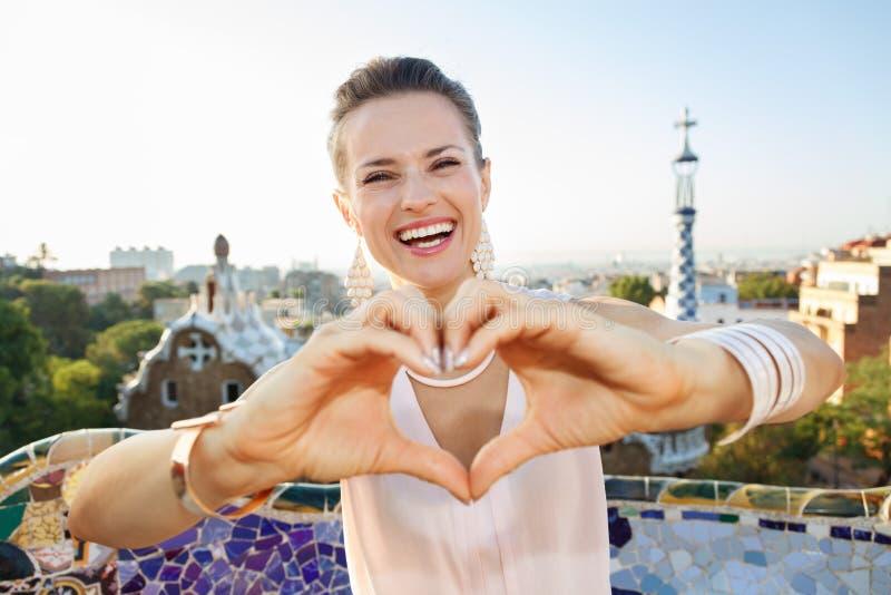 Kobiety turystyczny pokazuje serce kształtował rękę w Parkowym Guell, Barcelona zdjęcia stock