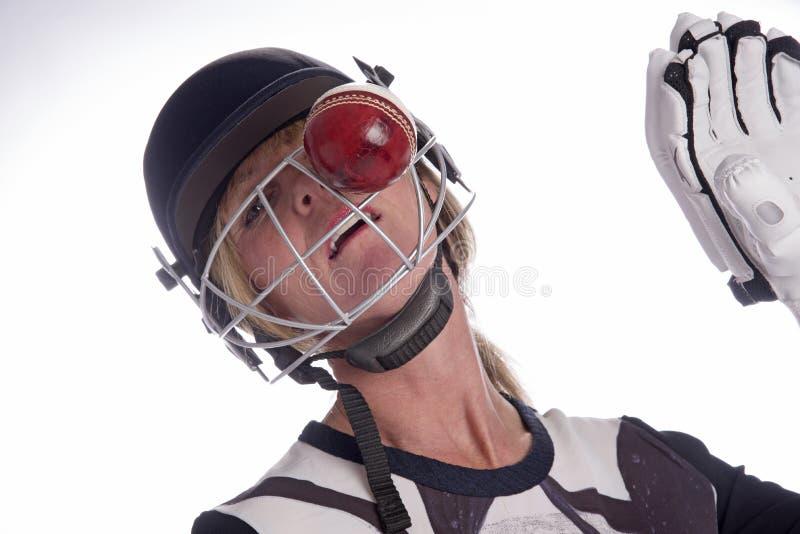 Kobiety twarz w hełmie uderza krykiet piłką zdjęcia royalty free