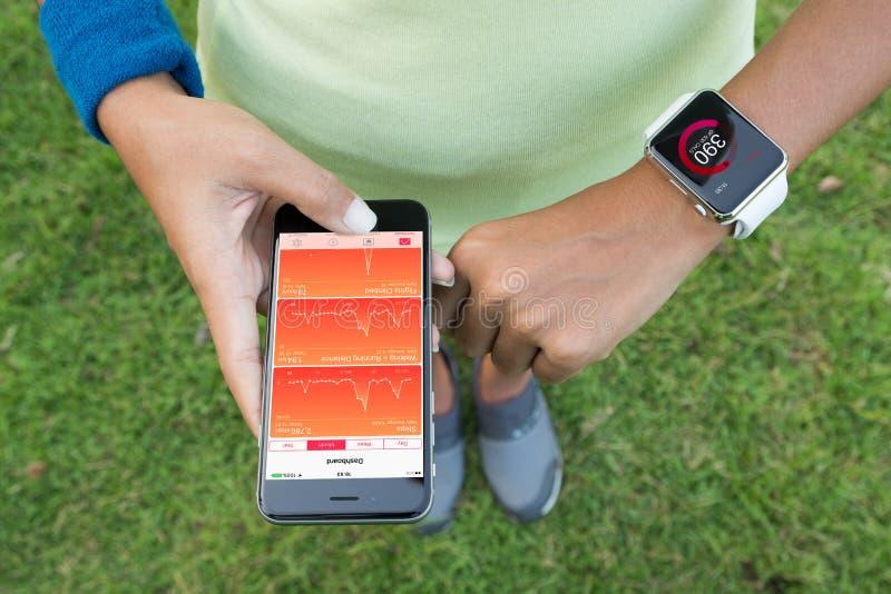 Kobiety używa iphone 6s i jabłczanego zegarek sprawdzają zdrowie app obrazy royalty free