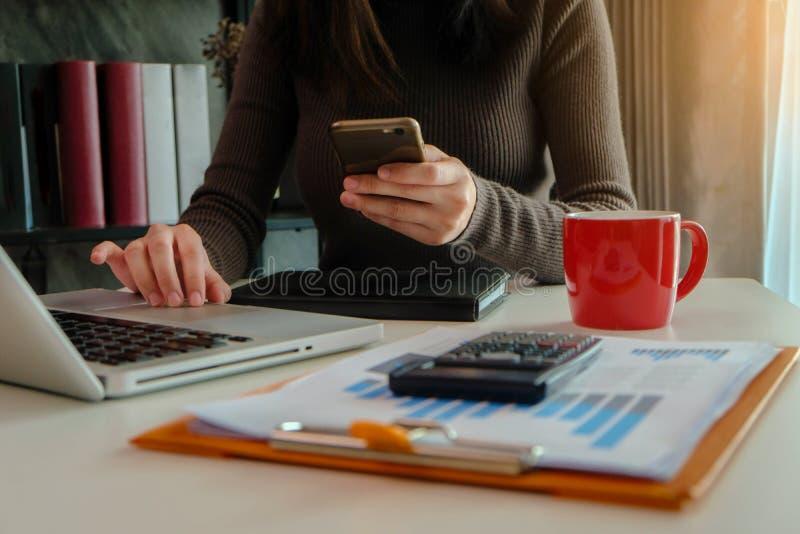 Kobiety używają smartphones i opodatkowywają kalkulatorów zdjęcia stock