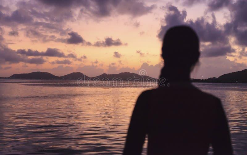 Kobiety uczucie Odświeżał z panoramą romantyczny zmierzchu niebo, morze w wieczór z złotym lekkim odbiciem na wodzie i Lato, zdjęcie stock