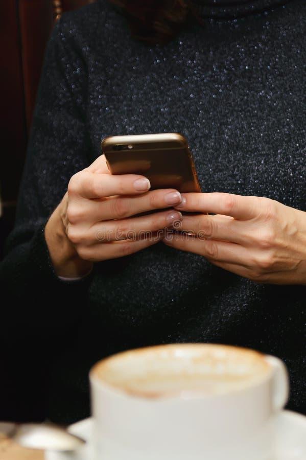 Kobiety use telefon komórkowy w sklep z kawą zdjęcie royalty free