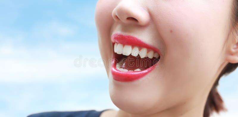 Kobiety usta uśmiech z wielkimi zębami nad błękitnym tłem obraz stock