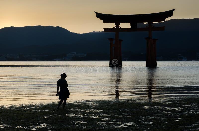 Kobiety w ciąży sylwetka blisko Torii - spławowa brama Miyajima wyspa przy zmierzchu czasem (Itsukushima) fotografia stock