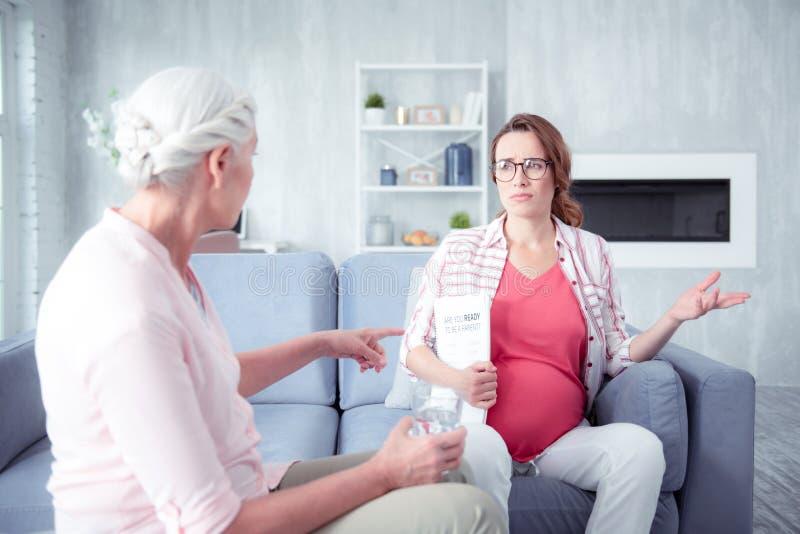 Kobiety w ciąży uczucie martwił się podczas gdy opowiadający jej matka zdjęcie stock