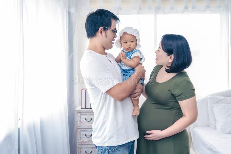 Kobiety w ciąży z mężem i pierwszy córką ma szczęśliwego czas wpólnie Osiem miesięcy kobiet w ciąży ma szczęśliwego czas z fotografia stock
