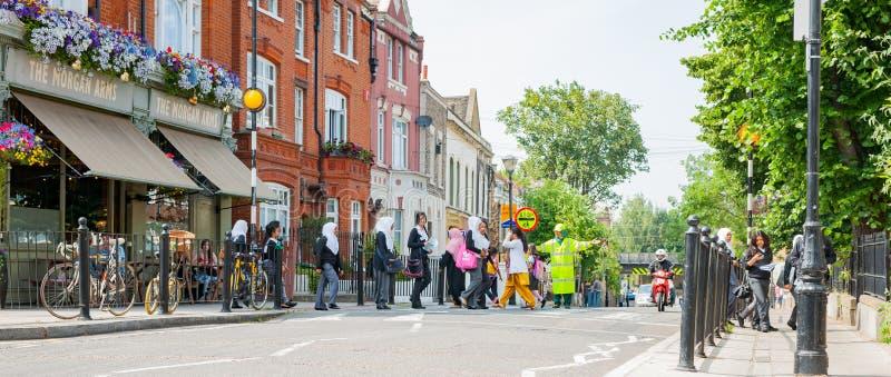 Kobiety w hijab wśród grupowego skrzyżowania ulicy w miastowej ulicznej scenie pokazuje nowożytną miasto różnorodność obrazy royalty free