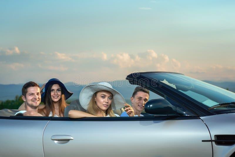 Kobiety w rondo szerokich kapeluszach siedzi w srebnym kabriolecie mężczyznach i zdjęcie stock