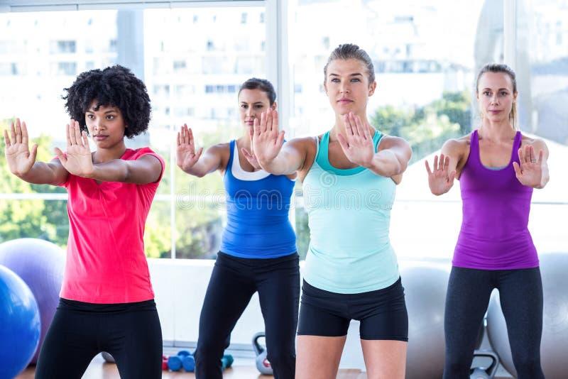 Kobiety w sprawności fizycznej studiu z rękami rozciągać naprzód zdjęcie stock