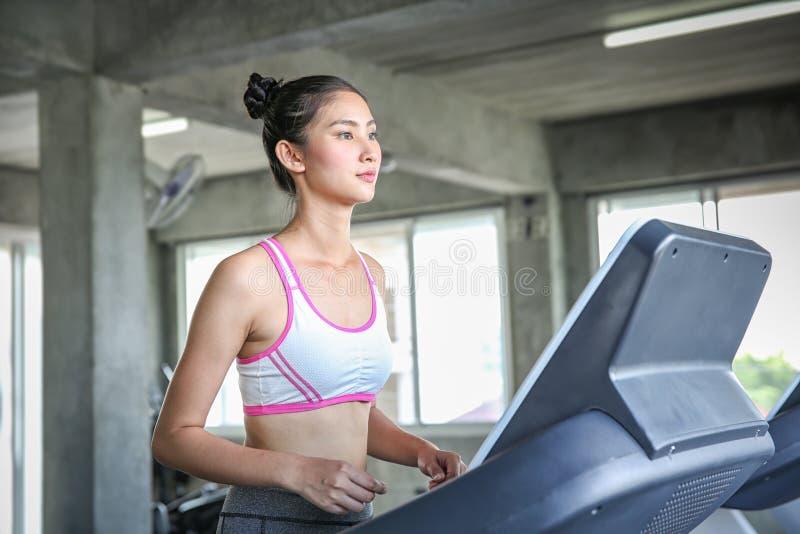 Kobiety wchodzić do ciężaru kontrolnego program Młodzi ludzie biega na karuzeli Młodej kobiety szkolenie w gym piękne fotografia royalty free