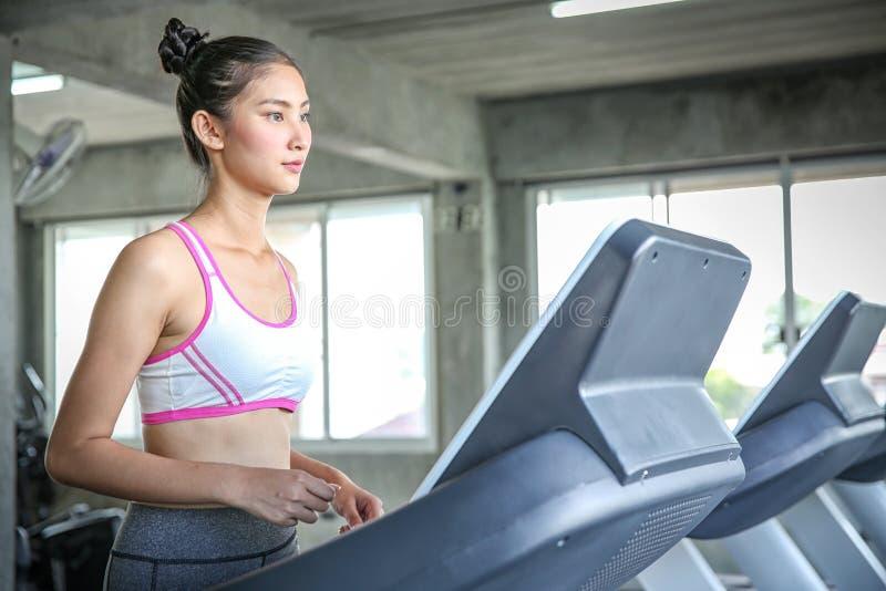 Kobiety wchodzić do ciężaru kontrolnego program Młodzi ludzie biega na karuzeli Młodej kobiety szkolenie w gym piękne zdjęcie royalty free