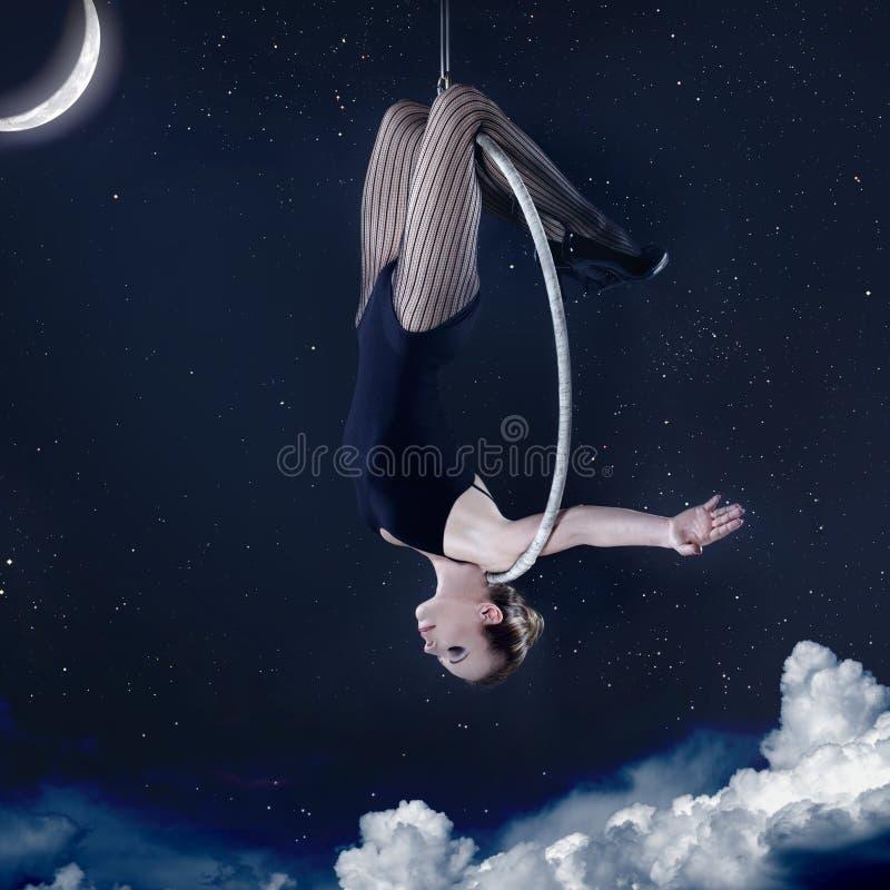 Kobiety wieszać do góry nogami na powietrznym obręczu przy nocą fotografia stock