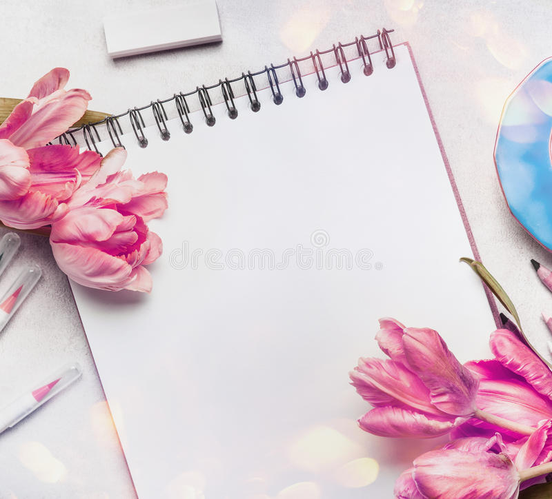 Kobiety wiosny workspace z jasnoróżowymi tulipanami, notatnik, sketchbook lub kolorowi szczotkarscy markiery, zdjęcie royalty free