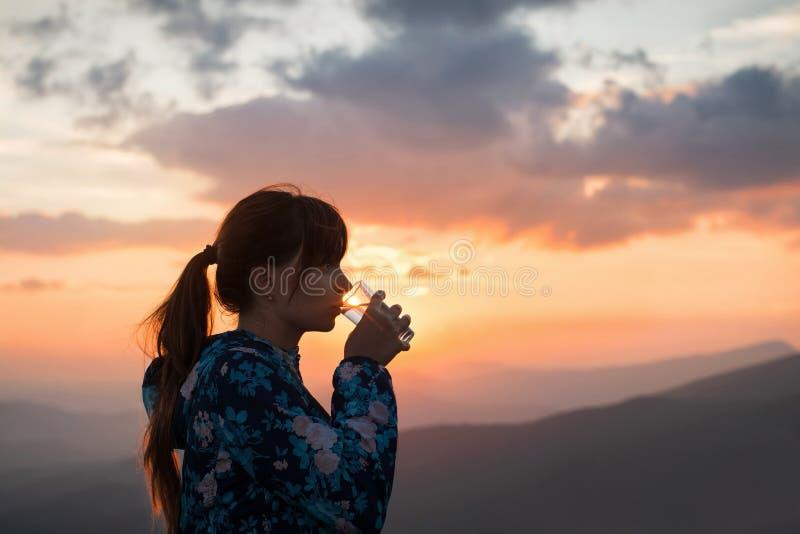 Kobiety woda pitna na zmierzchu tle fotografia stock