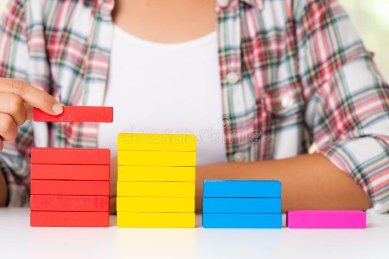 Kobiety wręczają stawiających kolorowych drewnianych bloki w formie schody zdjęcia royalty free