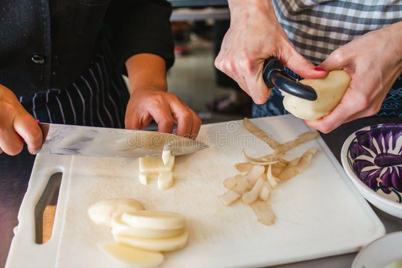 Kobiety wręczają tnące grule i kulinarnych warzywa sałatkowych w kuchni fotografia royalty free