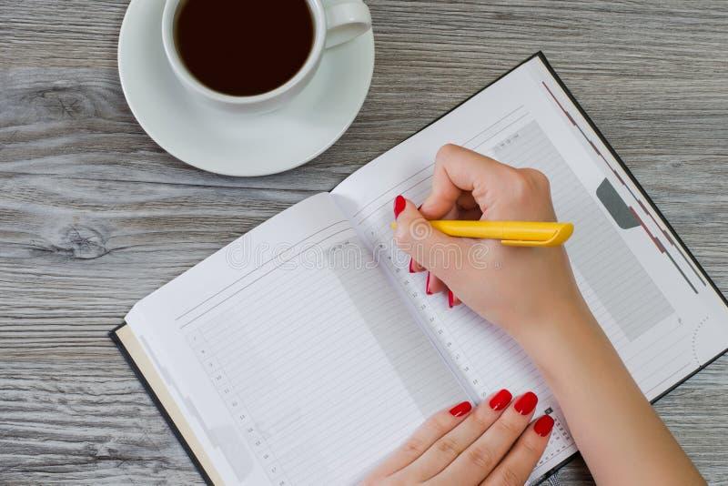 Kobiety writing esej w notepad przy stołem, filiżanka kawy jest o obraz stock