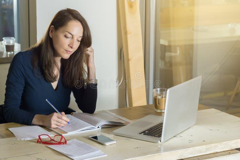Kobiety writing na notatnika obsiadaniu ma kawę i studiowanie zdjęcia royalty free
