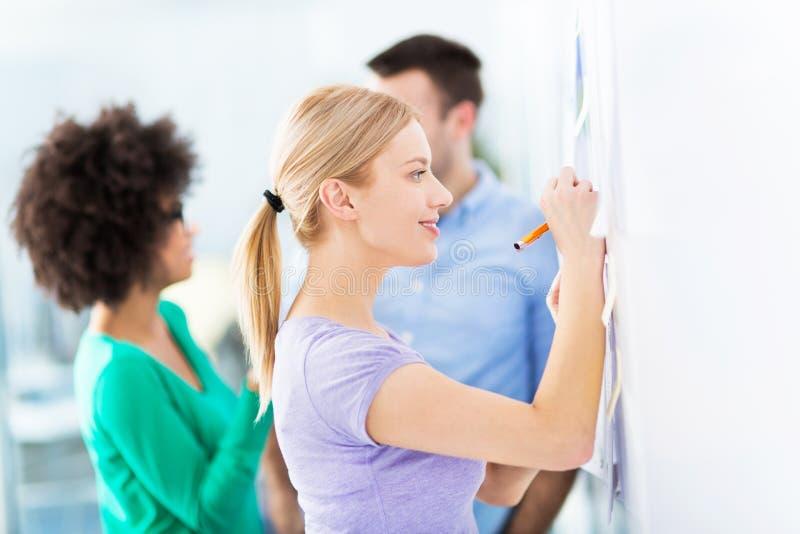 Kobiety writing pomysły na adhezyjnych notatkach zdjęcia royalty free