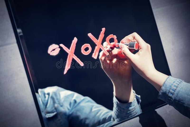 Kobiety writing xoxo na lustrze z czerwoną pomadką obraz stock