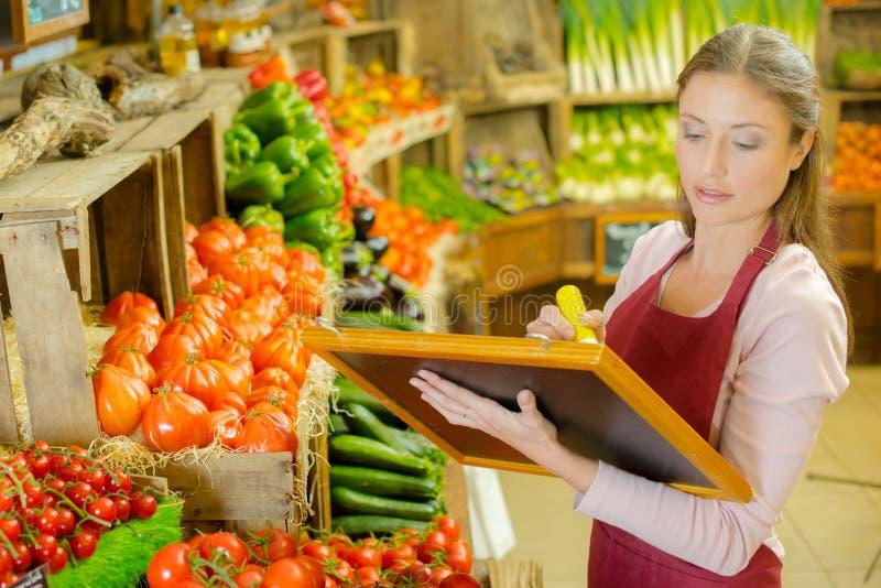 Kobiety writing znak dla owoc i veg obrazy stock