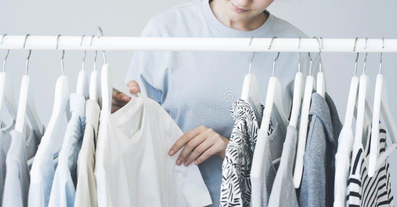 Kobiety wybierać odziewa na stojaku fotografia stock