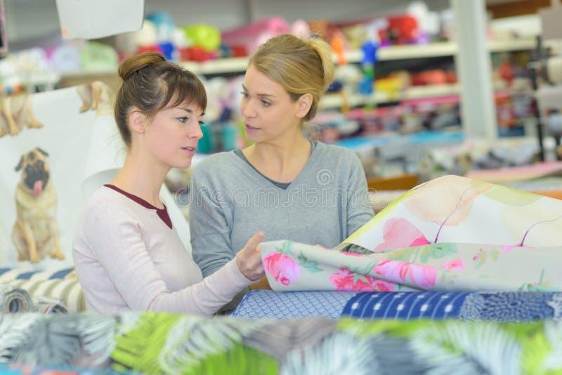 Kobiety wybiera tkaninę w tekstylnym hurtowym sklepie fotografia stock