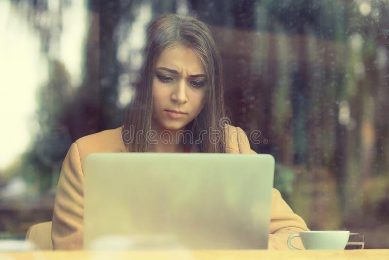 Kobiety wzburzony obsiadanie w kawiarni przed laptopu mienia ekranem wewnątrz zdjęcie stock