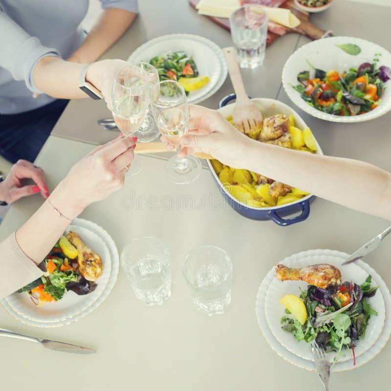 Kobiety wznosi toast z szampanem podczas gdy mieć gościa restauracji wpólnie obrazy stock