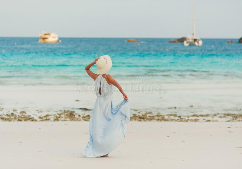 Kobiety wzorcowa dziewczyna w smokingowym i kapelusz pozuje przy tropikalną plażą zdjęcia royalty free