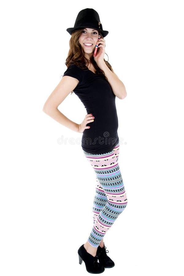 Kobiety wzorcowy opowiadać na jej telefonie komórkowym w kolorowych leggings obraz stock