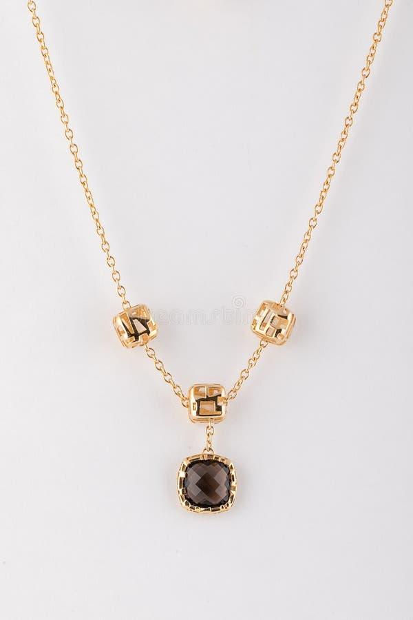 Kobiety złota łańcuch z czerń kamienia breloczkiem odizolowywającym na białym tle fotografia royalty free