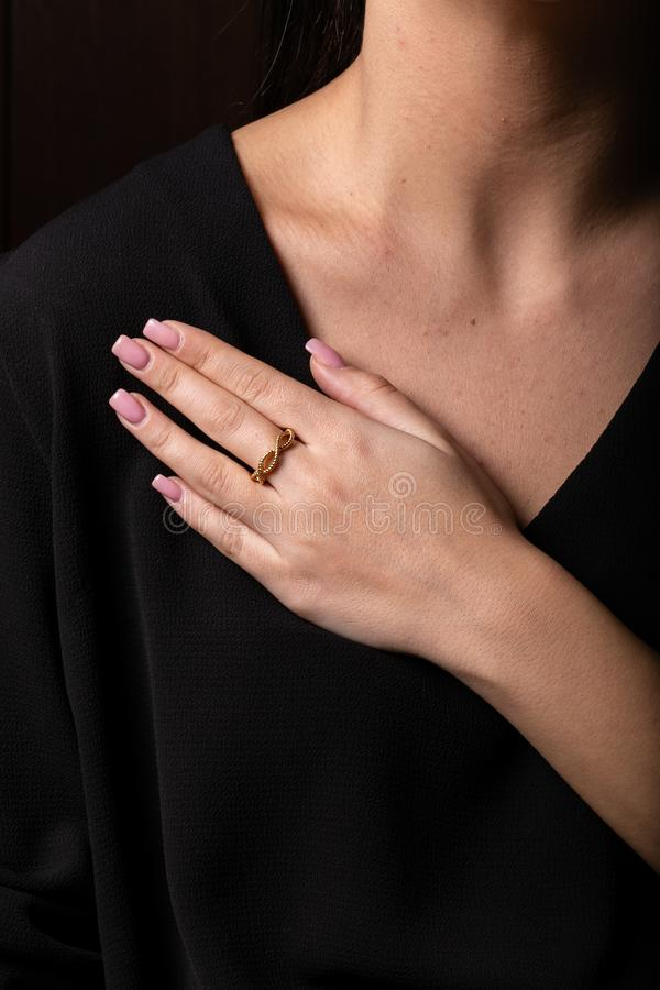 Kobiety złoto, przekręcający pierścionek na jej palcu na czarnym tle, fotografia royalty free